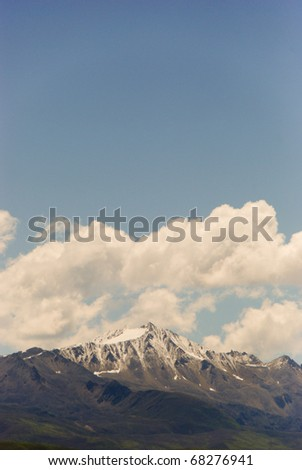 Cloudy Himalayan Mountain with fluffy clouds blowing over the peak in China - stock photo