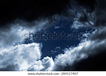 Cloudy night with a hole in the clouds revealing the stars - stock photo