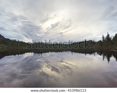 Cloudy reflection on Campbell Lake, Harrison Hot Springs, British Columbia - stock photo