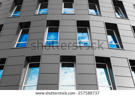 cloudy sky and glass silhouettes on modern building. - stock photo