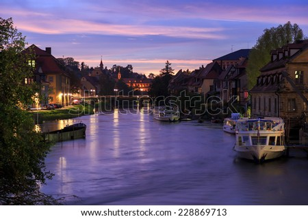 Cloudy sky at sunset, Regnitz river with ships in Bamberg, Germany  - stock photo