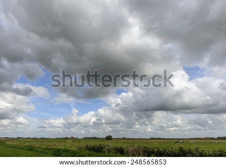 cloudy sky over Belgian plains near Oostende, landscape of meadows under a bright cloudy sky in the plains near Oostende, Belgium  - stock photo