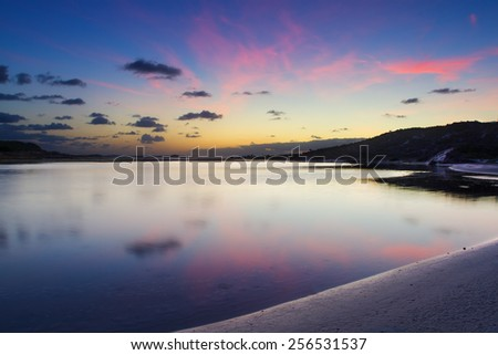 Cloudy sunrise over a quiet lagoon with cloud patterns reflected in the water - stock photo