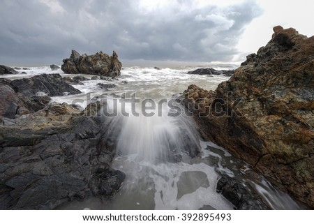 Cloudy sunrise seascape at Pandak Beach, Terengganu with waves splashing on coastal rocks. Soft focus due to long exposure shot. Nature composition - stock photo