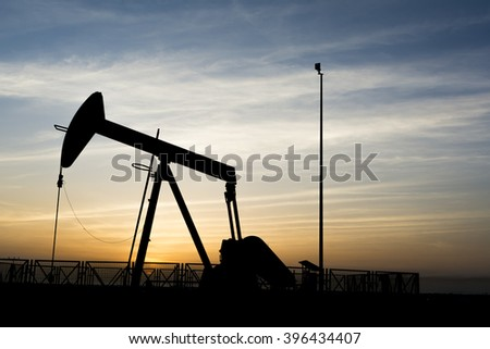 Cloudy sunset and silhouette of crude oil pump in oil field  - stock photo
