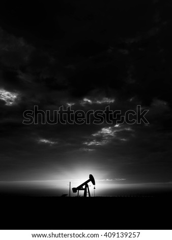 Cloudy sunset and silhouette of crude oil pumping unit in oilfield - Black and white  - stock photo