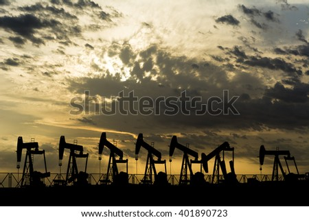 Cloudy sunset and silhouette of crude oil pumps in oil field. - stock photo
