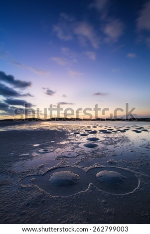 Cloudy sunset over a quiet lagoon with interesting patterns from sand heaps - stock photo