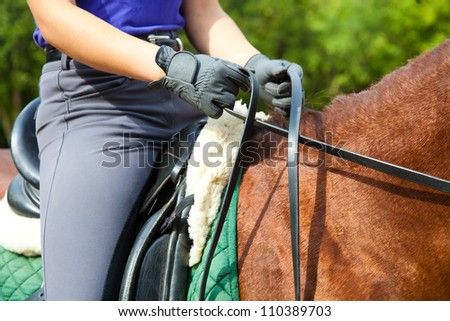Clouse-up of woman rider and horse - stock photo