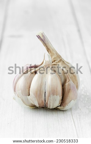 Clove of garlic over white wooden table - stock photo