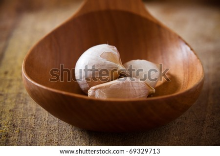 cloves of garlic in the wooden spoon - stock photo