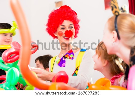 Clown at children birthday party entertaining the kids - stock photo