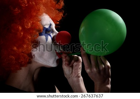 Clown blow up a balloon - stock photo