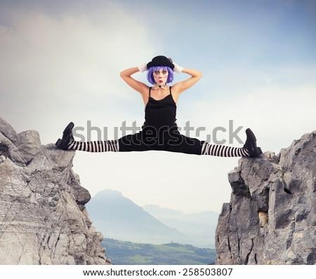 Clown dancer makes split between two mountains - stock photo