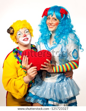 Clown giving his heart actress.Valentine day. Isolated on white - stock photo