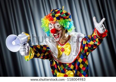 Clown in studio with loudspeaker - stock photo
