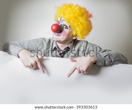 clown pointing fingers at the poster - stock photo