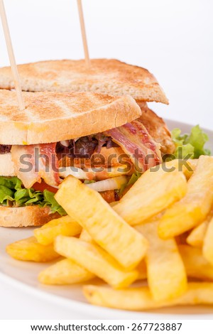Club sandwich on toasted white bread with a meat filling served with crispy golden potato French fries, closeup partial view isolated on white - stock photo