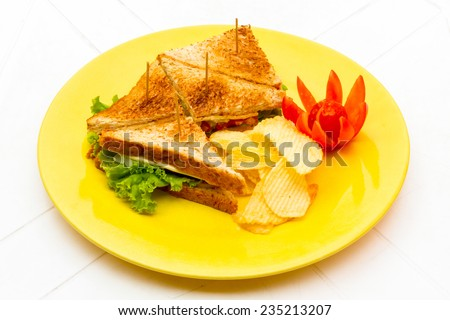 club sandwich with Cheese bacon, ham, tomato, lettuce, and garnished with a pickle at a diner. Freshly made - stock photo