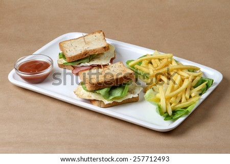 Club sandwich with ham and pork fried bacon, baked egg topped with cheese and lettuce next to a glass bowl of fresh hot red tomatoes ketchup and fine crispy baked french fries - stock photo