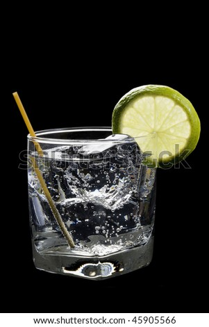 Club soda or Gin or Vodka and tonic with lime slice garnish on a black background - stock photo