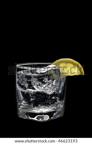 Club soda or Vodka / Gin and tonic mixed drink with lemon slice on a black  background - stock photo