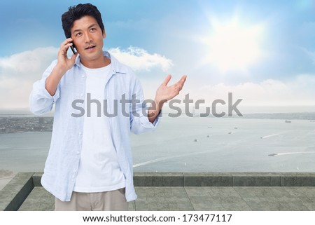 Clueless male on his cellphone against coastline city - stock photo