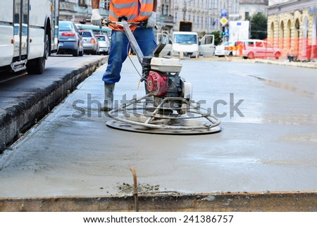 CLUJ-NAPOCA, ROMANIA - CIRCA JULY 2014: Construction worker finishes concrete slab with trowel machine by road upgrade. Road segments are partially closed for traffic on one of the main streets. - stock photo