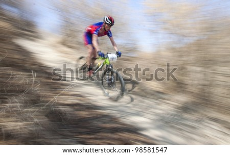 "CLUJ-NAPOCA, ROMANIA - MARCH 24: Unidentified competitor during the Clujul Pedaleaza mountain bike competition, 1st stage ""Napolact"" on March 24, 2012 in Cluj-Napoca, Romania. - stock photo"