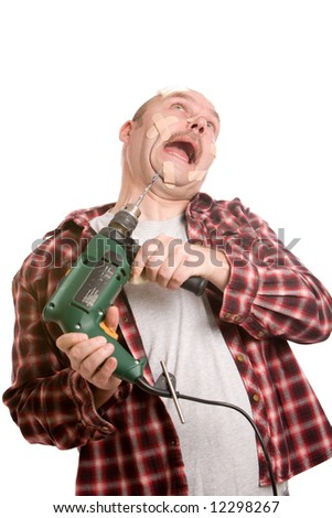 Clumsy handyman struggling with the drill while having his face already covered in bandaids - stock photo