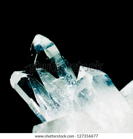 Cluster of rock crystals or pure quartz, a clear macrocrystalline variety of silica (SiO2) isolated on black background. This gemstone is said to have strong healing power. Birthstone for April. - stock photo