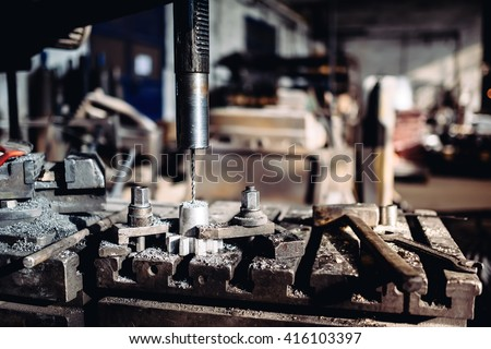 CNC Drilling machinery lathe working with steel and iron pieces at industrial factory - stock photo