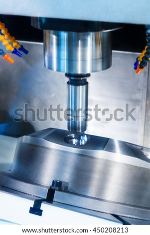 CNC milling machine during operation. Produce drill holes in the metal part. - stock photo