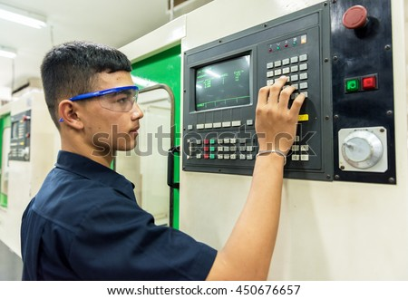 CNC operator, mechanical technician worker at metal machining milling center in tool workshop inserting data with keyboard wearing (Focus on keyboard) - stock photo