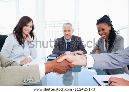 Co-workers shaking hands while their director and two executives watching them - stock photo