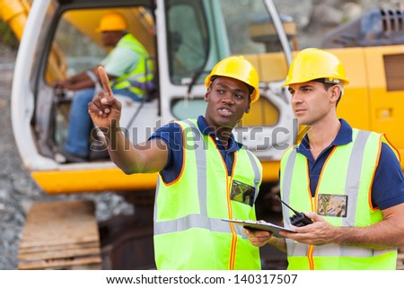 co-workers talking at construction site with bulldozer behind them - stock photo