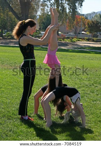 Coach and her gymnasts in the park - stock photo