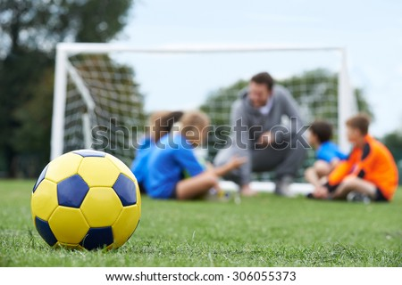 Coach  And Team Discussing Soccer Tactics With Ball In Foreground - stock photo