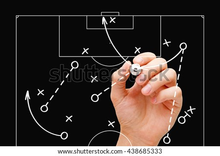 Coach drawing soccer play tactics with white marker on transparent wipe board over black background. Football manager explaining game strategy. - stock photo