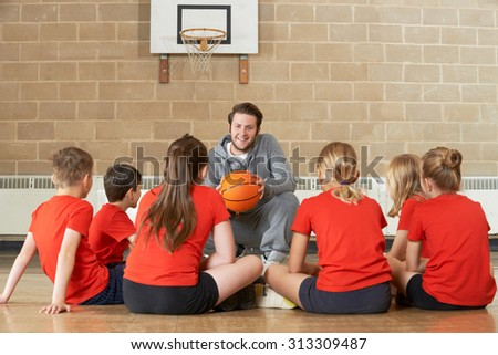 Coach Giving Team Talk To Elementary School Basketball Team - stock photo