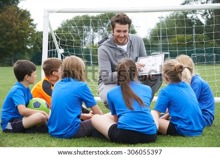 Coach Giving Team Talk To Elementary School Soccer Team - stock photo