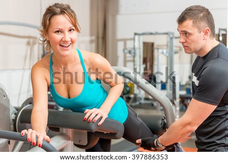 coach helps girl at the gym doing exercises - stock photo