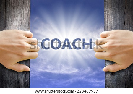 Coach text in the blue sky behind hand opening a wooden door. - stock photo