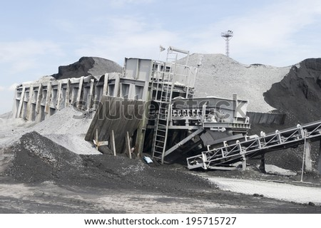 Coal depot in the Rotterdam Harbor. The conveyor belt leads from the sea ships to the smaller river ships. - stock photo