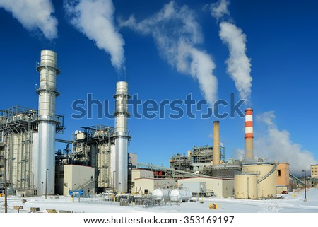 Coal Fossil Fuel Power Plant Smokestacks Emit Carbon Dioxide Pollution On A Cold Snowy Day - stock photo