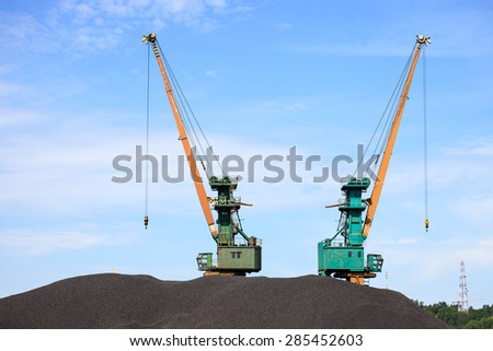 Coal industry - A massive pile of coal and cranes. - stock photo
