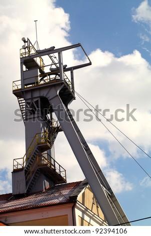 Coal mine headgear tower on blue sky - stock photo