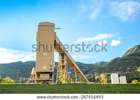 Coal mine infrastructure among beautiful mountains and green grass of USA - stock photo