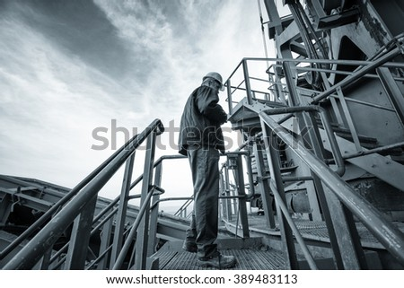 Coal mine worker with a helmet on his head standing in front of huge drill machine and looking at it. Side view. Image is carefully post processed and toned. - stock photo