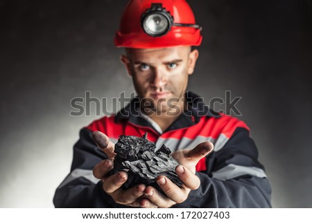 Coal miner holding lump of coal against a dark background - stock photo